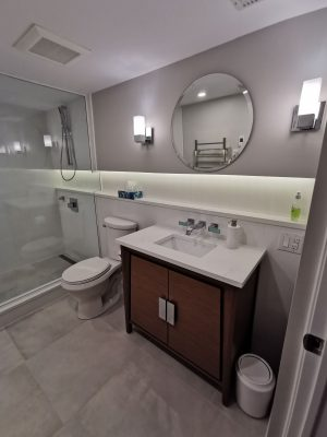 modern bathroom with brown vanity and backlit build in storage space